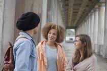 Multi-ethnischen Jugendliche sprechen während Sie stehen im Korridor, Berlin, Deutschland — Stockfoto