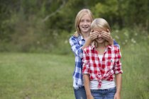 Girl covering friend 's eyes — стоковое фото