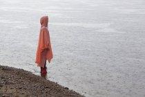 Жінка в плащ стоїть на березі озера під час сезону дощів — стокове фото