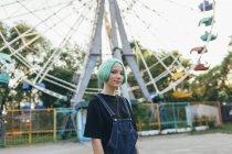 Портрет улыбающейся девочки-подростка, стоящей напротив колеса обозрения в парке — стоковое фото