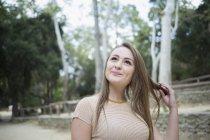 Задумчивая молодая женщина играет с волосами в парке — стоковое фото