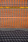 Высокий угол обзора оранжевого забора с тенью на дороге — стоковое фото