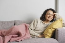 Thoughtful woman smiling while relaxing on sofa at home — Stock Photo