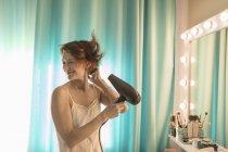 Mujer sonriente de pie frente al espejo en el tocador - foto de stock