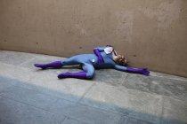 Unconscious superhero lying on footpath against wall — Stock Photo