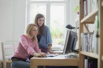 Young female friends using computer at home — Stock Photo