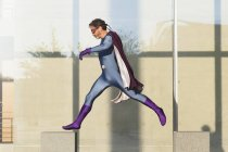 Superhero jumping on concrete against glass wall — Stockfoto
