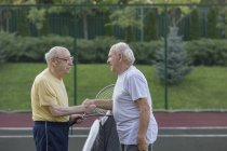 Senior friends shaking hands over net at tennis court — Stock Photo