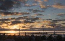 Blick auf Brücke und Skyline vor wolkenverhangenem Himmel bei Sonnenuntergang, Melbourne, Victoria, Australien — Stockfoto