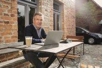 Retrato de hombre maduro con portátil sentado en el patio trasero - foto de stock