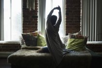 Rear view of woman stretching on bed at home — Stock Photo