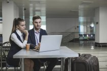 Young business couple using laptop at table in airport — Stock Photo