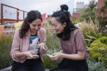Счастливые подруги используют смартфоны, сидя на патио — стоковое фото