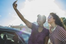 Happy young woman taking selfie with female friend at car against sky — Stock Photo