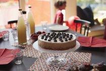 Торт на підставці за пляшки столом з дівчинка грає у фоновому режимі — стокове фото