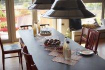 Vista de ángulo alto de las luces colgantes que cuelgan sobre la comida servida en la mesa de comedor en casa - foto de stock