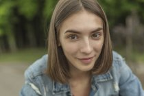 Ritratto di giovane donna sorridente con capelli marroni all'aperto — Foto stock
