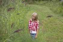 Girl in a meadow smiling to camera — Stock Photo