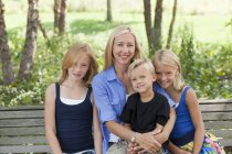 Mom and three kids on a bench — Stock Photo