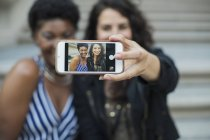 Woman taking selfie with young female friend with mobile phone — Stock Photo
