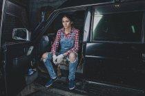 Ritratto di meccanico donna sicura seduta in macchina in officina — Foto stock