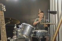 Ragazzo che gioca tamburo contro muro di casa — Foto stock