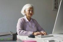 Portrait de femme senior à l'aide d'ordinateur tout en restant assis contre le mur du Bureau — Photo de stock