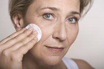 Woman cleaning face with cotton pad — Stock Photo