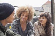 Sorridente giovani amici parlando mentre seduto nella giornata di sole — Foto stock