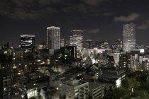 Prédios iluminados na cidade contra o céu à noite — Fotografia de Stock