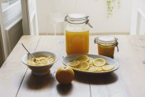 Still life of citrus fruit sauces and preserves on table — Stock Photo