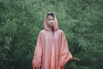 Young woman wearing raincoat standing amidst plants during rainy season — Stock Photo