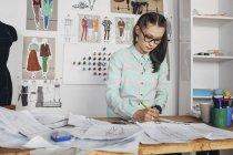 Dessinateur de mode esquisses à l'établi en studio — Photo de stock