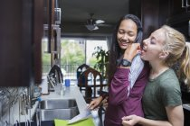 Happy woman feeding girlfriend with fruit in kitchen at home — Stock Photo