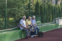 Senior friends with tennis rackets sitting against fence at court — Stock Photo
