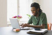 Glücklicher Mann mit Laptop am Tisch im Haus — Stockfoto