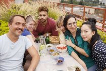 Портрет щасливі чоловічих і жіночих друзів, сидячи за столом відкритий в patio — стокове фото