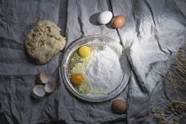 Directly above shot of eggs and flour on tray at table — Stock Photo