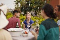 Glücklich männliche und weibliche Freunde sitzen am Tisch im Freien auf der Terrasse — Stockfoto