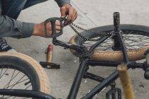 Обтинання чоловіки руки ремонту велосипедів ланцюг на вулиці — стокове фото