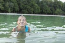 Portrait of smiling girl swimming in lake — Stock Photo