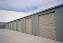 Exterior of warehouse with rolling garage doors — Stock Photo