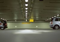 Surface level view of cars in underground parking lot — Stock Photo