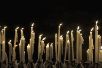 Righe di fiamme tremolanti delle candele sopra il nero — Foto stock