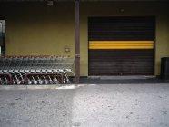 Shopping carts row next to industrial door — Stock Photo