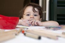 Little boy leaning on table littered with colored pencils and art supplies — Stock Photo