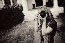 Портрет молодой девушки, прицеливающейся с камерой во дворе — стоковое фото