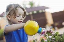 Une jeune fille arrosant une fleur avec un arrosoir jouet — Photo de stock