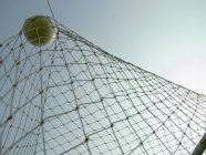 Soccer ball in a goal with clear sky on background — Stock Photo
