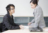 Un hombre y una mujer teniendo una reunión de negocios en una sala de conferencias - foto de stock
